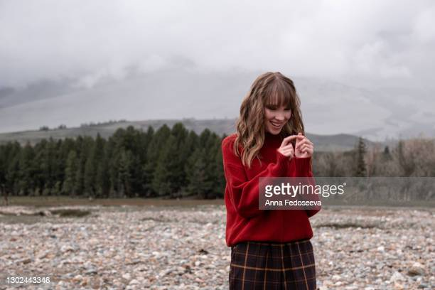 a young graceful girl walks in the bed of a dry river. mountain altai nature. tourist trip. beautiful girl in a red knitted sweater. - russia stock pictures, royalty-free photos & images