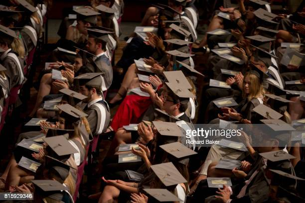 Young graduates wearing rented gowns and mortarboards applaud a speech in the central hall of their university during their graduation ceremony on...