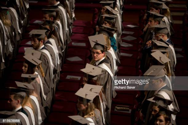 Young graduates wearing rented gowns and mortarboards sit in the central hall of their university waiting for their graduation ceremony to start on...