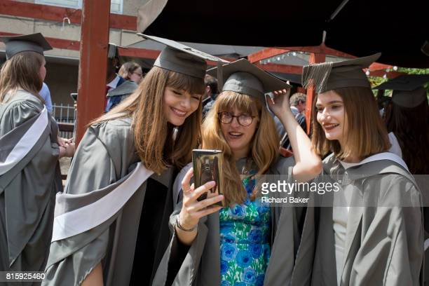 Young graduates wearing rented gowns and mortarboards smile for their selfie photo at a private party before their university graduation ceremony on...