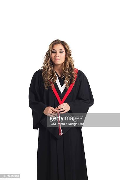 Young graduating woman holding her graduation cap and contemplating her graduation