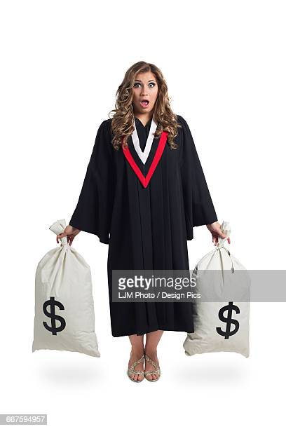 Young graduating woman holding money bags to symbolize the costs of her education