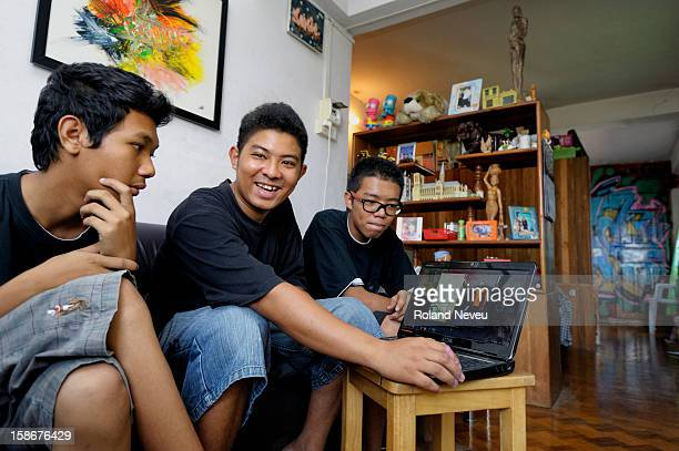 Young graffiti artist Sonic at home with 2 friends watching some internet on his laptop