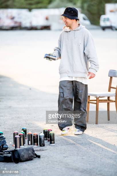 young graffiti artist walking and shaking spray can - baggy pants stock photos and pictures