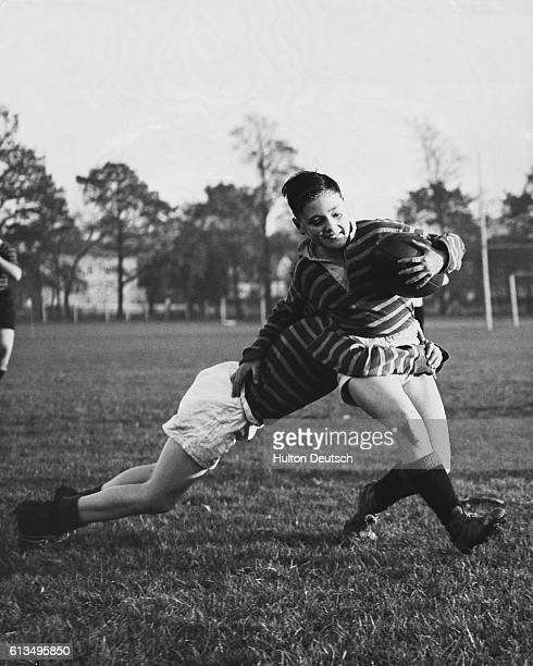 Young Graham Vartainin launches a tackle on Peter Wood during a rugby match on Morden playing fields Both are pupils from the Sir William Collins...