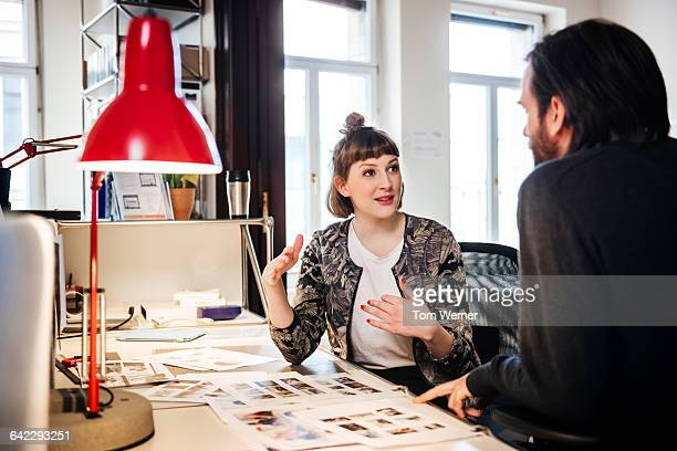 Young graphic designer talking with colleague