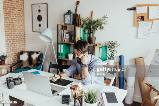 Young graphic designer working in his home office