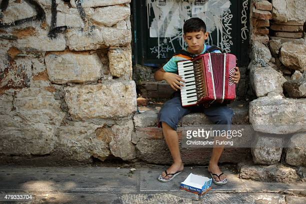 A young Greek boy plays his accordion for Euro's and Cents from tourists ahead of Sunday's referendum on July 3 2015 in Athens Greece The 'Yes' and...