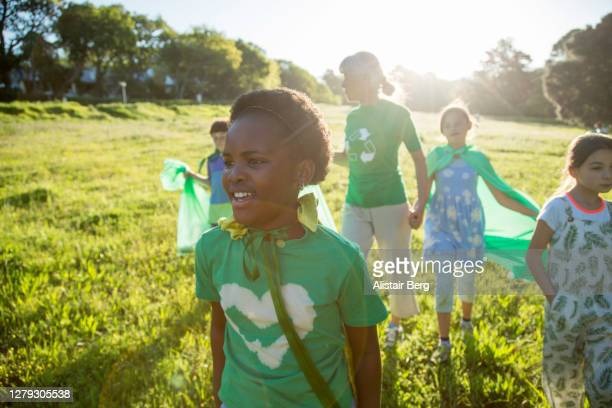 young green activists picking up litter in nature - campaigner stock pictures, royalty-free photos & images