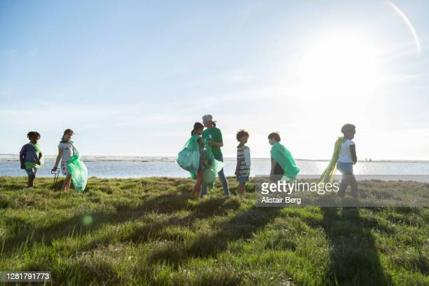 young green activists picking up litter in nature - charity and relief work stock pictures, royalty-free photos & images