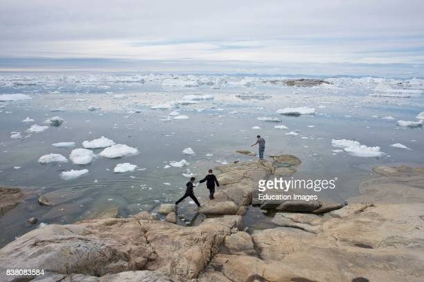 Young Greenlandic boys play by the water in Ilulissat West Greenland. The developments towards a modern society are moving fast in many parts of the...