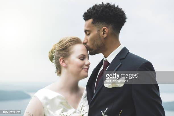 Young groom kisses bride's forehead