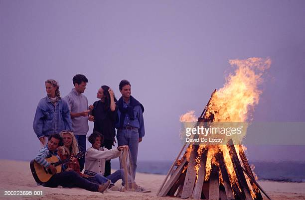 Young group of friends beside bonfire on beach