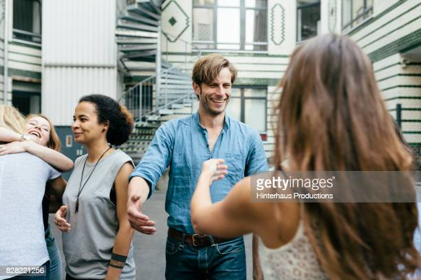 young group of friends greeting each other in courtyard - bella ciao foto e immagini stock