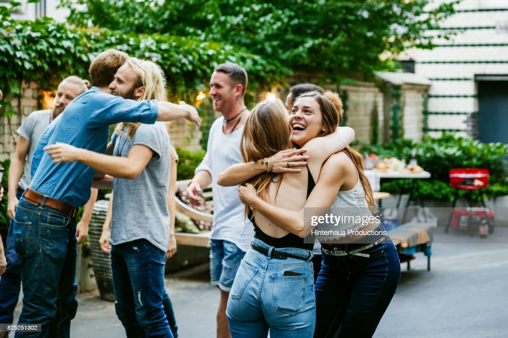 Young Group Of Friends Meeting Up For Barbecue, Hugging And Greeting Each Other. : Stock Photo
