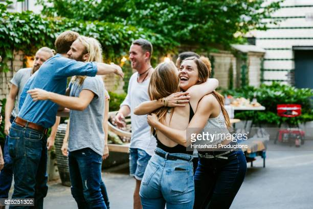young group of friends meeting up for barbecue, hugging and greeting each other. - outdoor party stock pictures, royalty-free photos & images