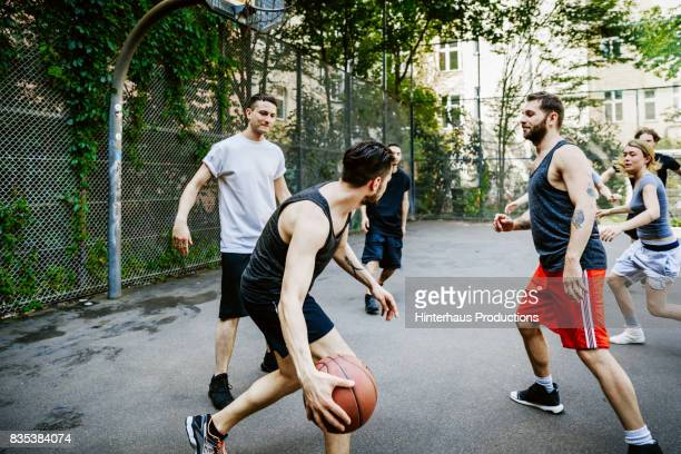 Young Group Of friends Playing Basketball Outdoors Together