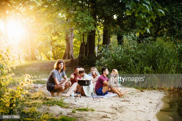 young group of friends sitting down for barbecue by lake together - capital cities stock photos and pictures