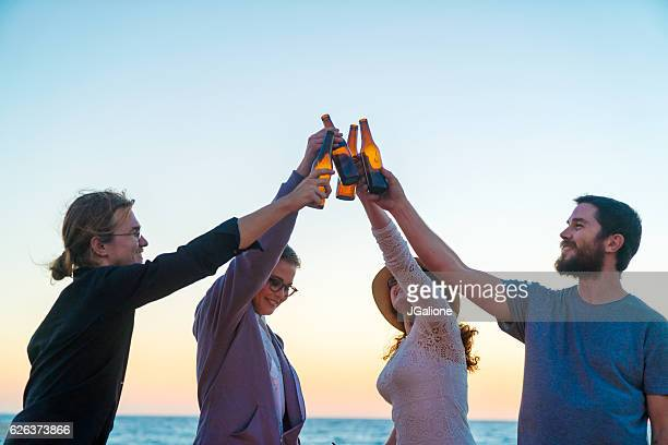 Young group of friends toasting with beer bottles