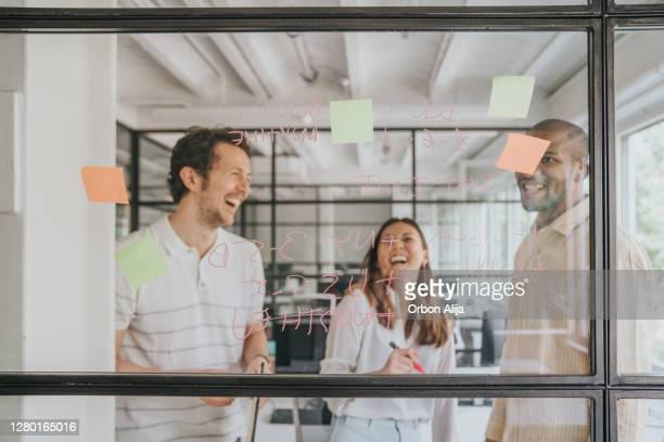 grupo joven de profesionales desarrollando estrategia de negocios - compromiso de los empleados fotografías e imágenes de stock