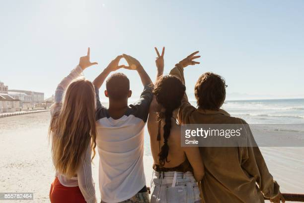 Young group shot from behind spelling love with hand gestures on beach