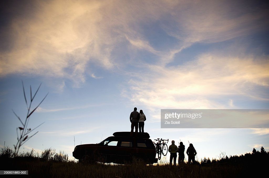 Young group watching sunset beside SUV, couple on car roof, rear view : Stock Photo