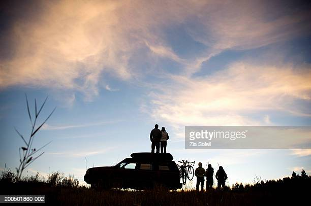 young group watching sunset beside suv, couple on car roof, rear view - palanquin stock photos and pictures