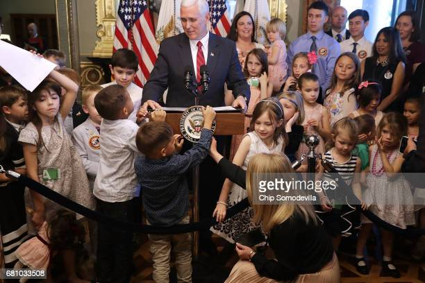 A young guest tries to remove the seal from the lectern as Vice President Mike Pence delivers remarks during and event with military families to...