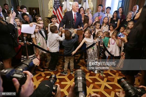 A young guest tries to remove the seal from Vice President Mike Pence's lecturn as he delivers remarks during and event with military families during...