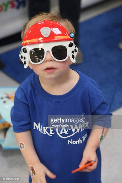 'DALLAS TEXAS APRIL 29 A young guest trying out some swag at the MakeAWish and Toys'R'Us birthday celebration for Wish Kid Mason on World Wish Day at...