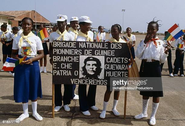 Young Guinean men and women hold a banner displaying a portrait of Che Guevara and the translation Pioneers of Guinea National Brigade Cadet Branch E...