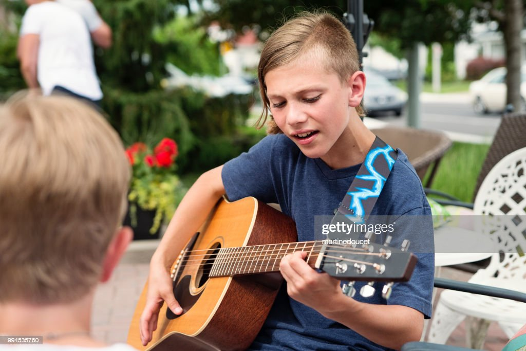 Young guitar player rehearsing before show in family driveway. : Foto de stock