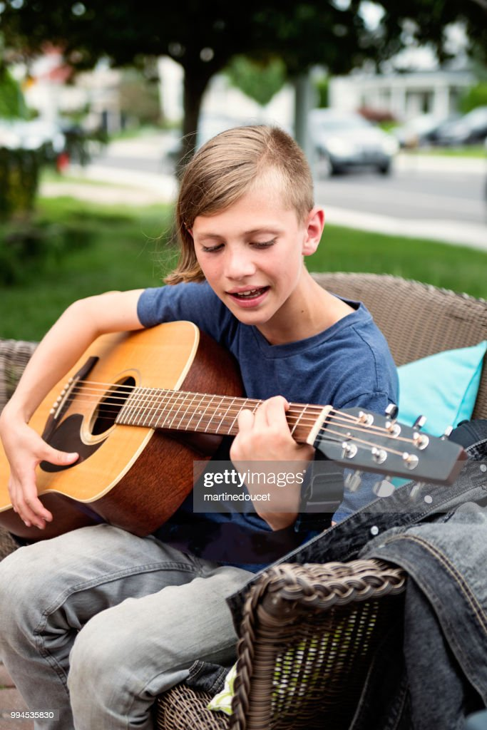 Young guitar player rehearsing before show in family driveway. : Stock Photo