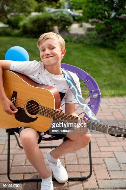 Young guitar player rehearsing before show in family driveway.