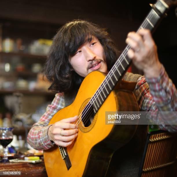若いギタリストにギターを弾くバー - ギタリスト ストックフォトと画像