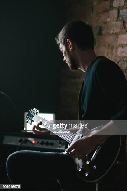 Jonge gitarist gitaarspelen met Tablet op versterker