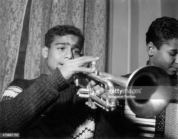 'A young guy blowing a trumpet testing himself with music alongside his friend wielding an accordion both in a band of mulatto kids at the Village of...