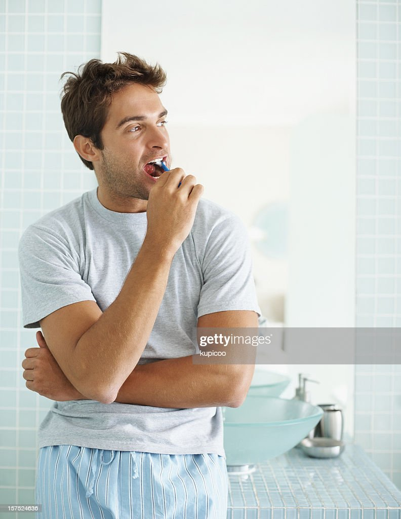 Young guy brushing his teeth in  the bathroom : Stock Photo