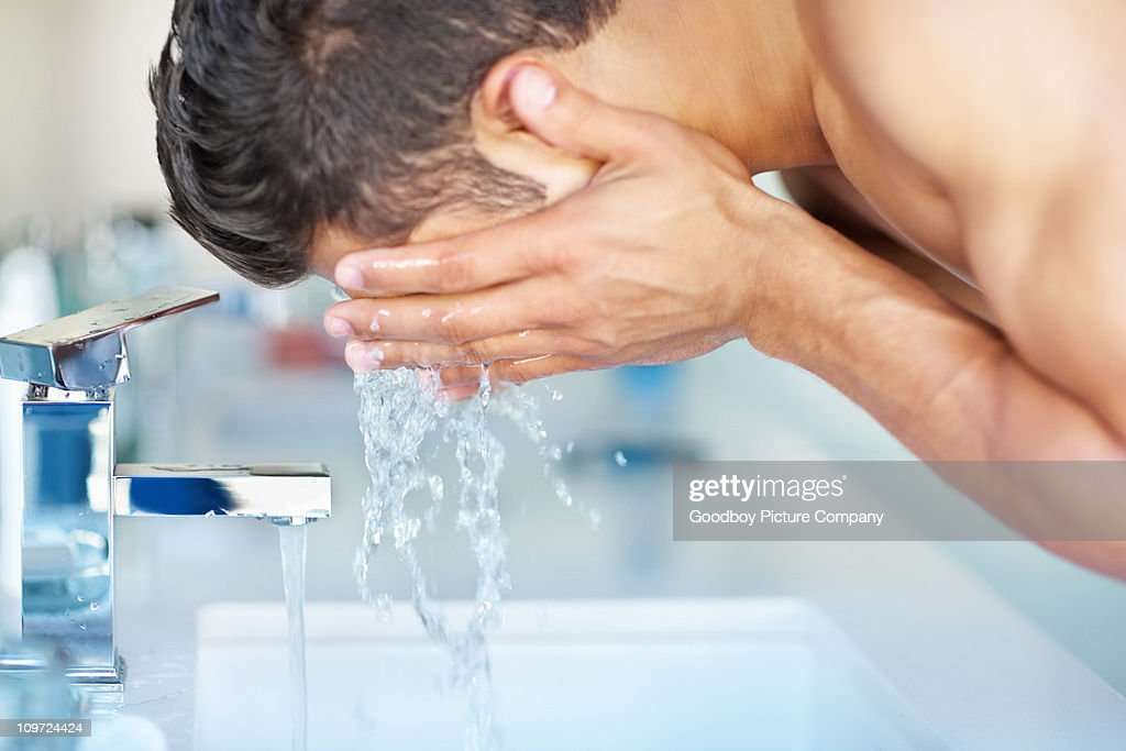 Young guy cleansing face with water at the sink : Stock Photo