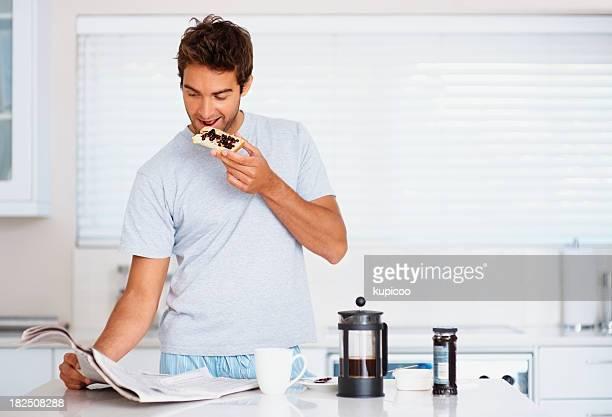 Junger Mann mit einem Frühstück white lesen Zeitung