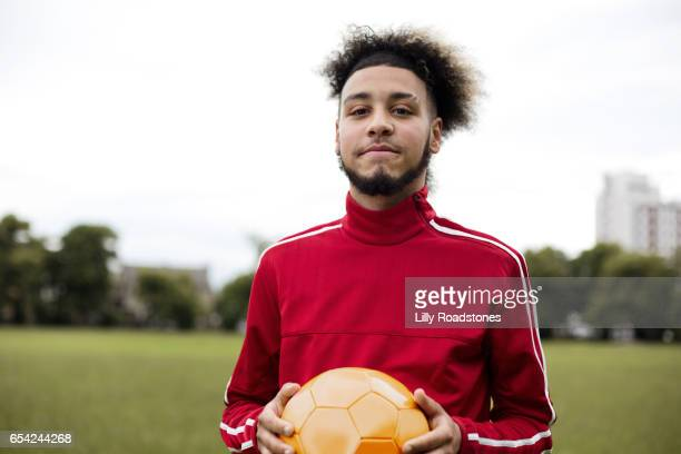 young guy holding ball in park - football player stock pictures, royalty-free photos & images
