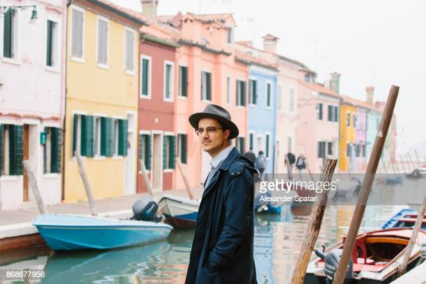 Young guy in hat and glasses standing near the canal in Burano, Italy