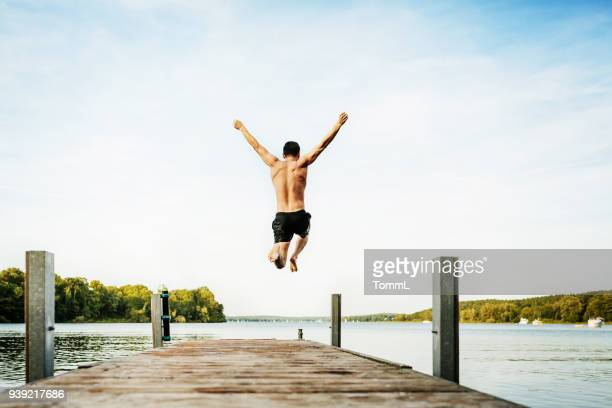 young guy jumping off jetty at lake - jetty stock pictures, royalty-free photos & images