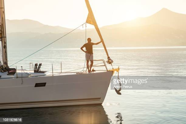young guy on the bow of the yacht at sunset - yacht de luxe photos et images de collection