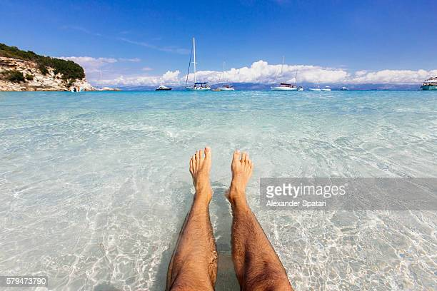 Young guy relaxing in the crystal clear waters with personal perspective view at the beach on Antipaxos island, Greece
