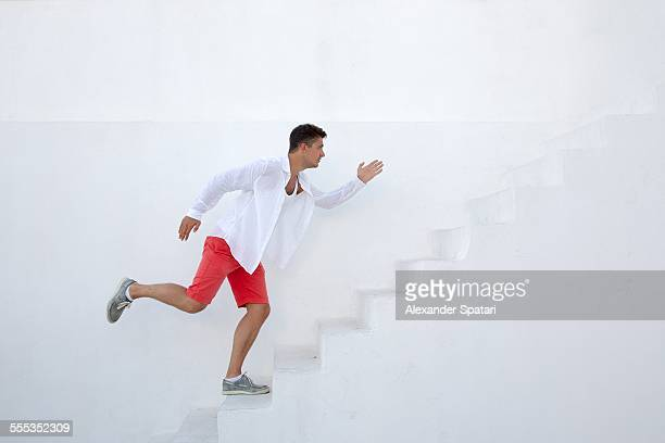 Young guy running up the stairs on white backgroun