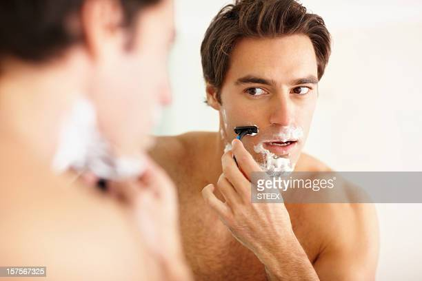 Young guy shaving in the bathroom with a razor