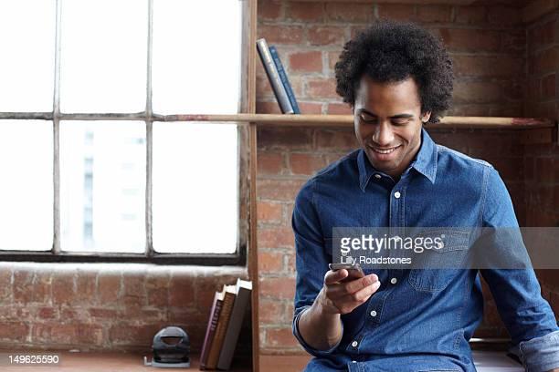 young guy sitting on desk using smartphone - mezzo busto foto e immagini stock