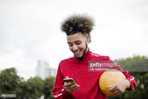 young guy texting while holding ball - football player stock pictures, royalty-free photos & images