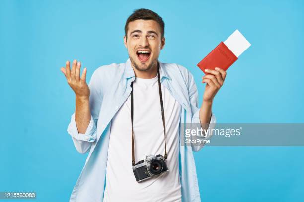 young guy tourist with a passport and tickets in his hands with a camera on his neck shrugs. - emigration and immigration stock pictures, royalty-free photos & images